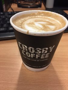 A small paper, takeaway cup of coffee from Crosby Coffee on a desk.